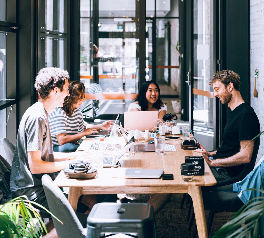 Cowoking yta med fyra unga männksor osm sitter vid vars en dator